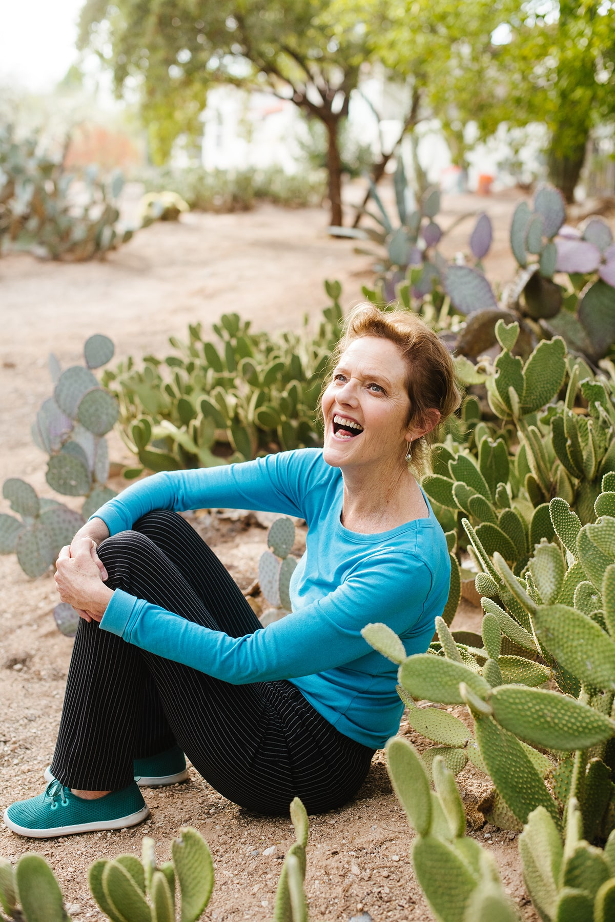 Nell sitting in front of several cactus plants in the Arizona desert