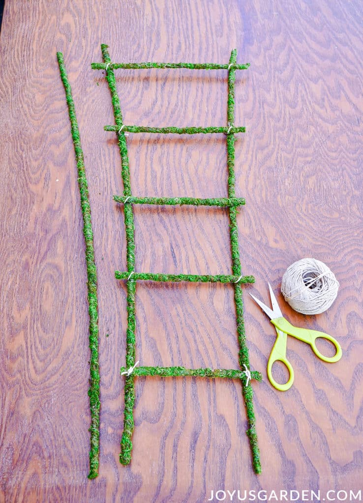 a homemade moss trellis sits on a work table next to a ball of twine & a pair of scissors