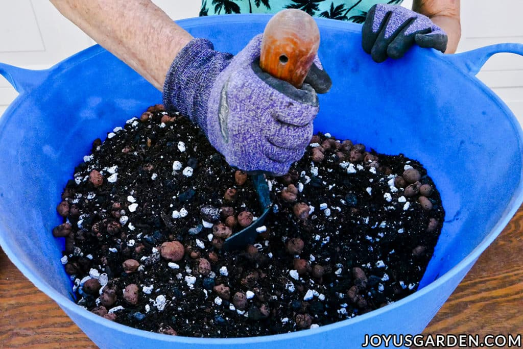 a hand holding a trowel blends soil mix in a blue tub