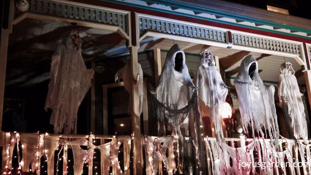 5 large ghouls are displayed on a front porch for halloween