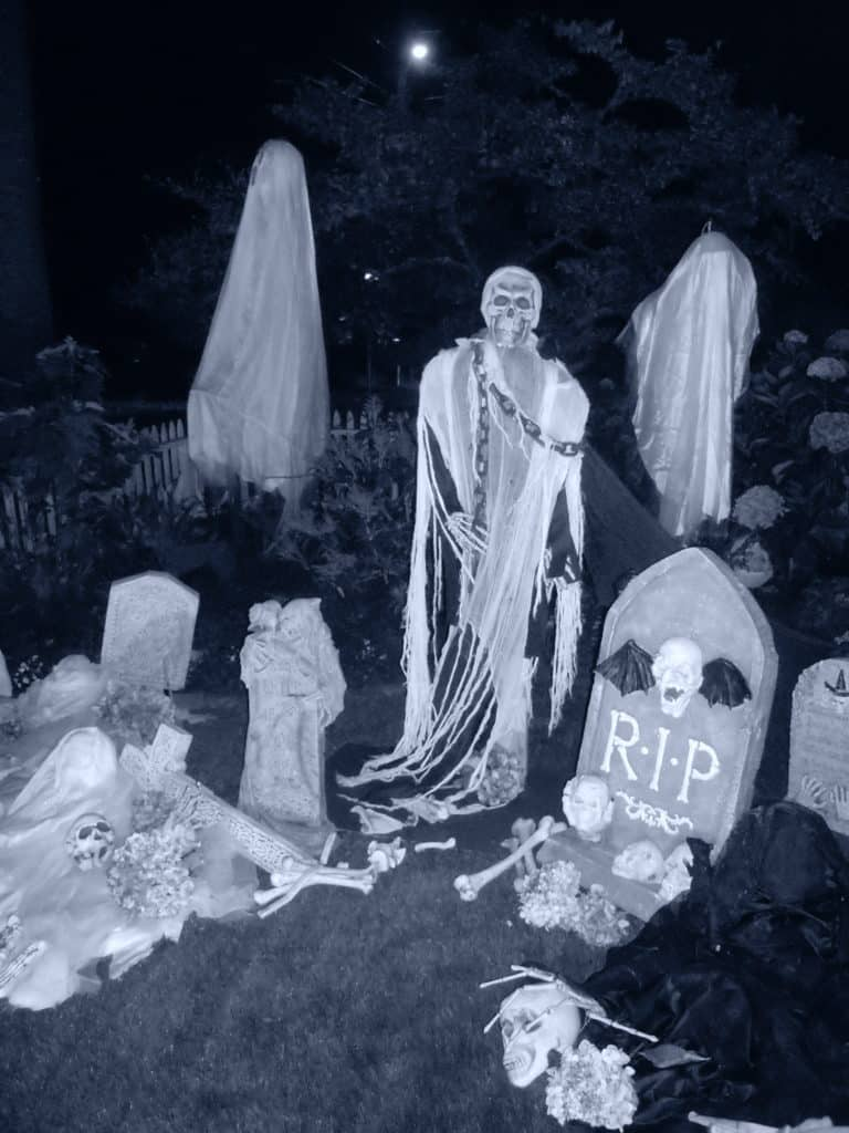 black and white photo of halloween decor, skulls, tombstones
