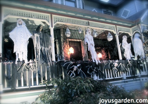 force porch with white railing decorated with ghosts for halloween
