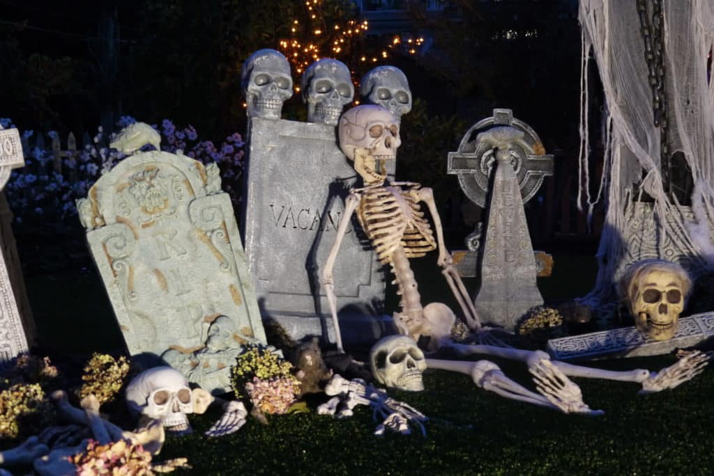 halloween decor skeletons leaning up against decorative tombstones