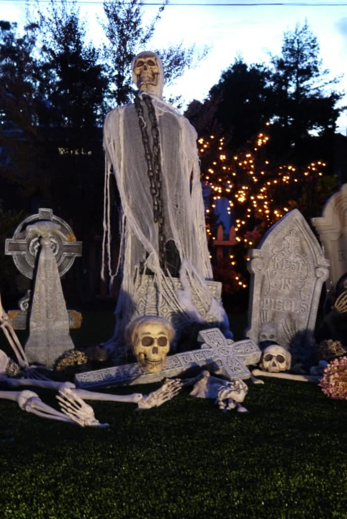 a larger ghoul stands over a halloween cemetery scene at night