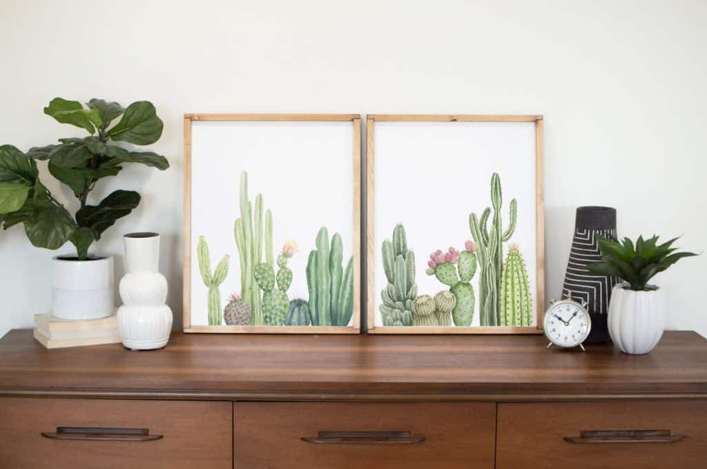 two prints of green cacti with pink flowers on a dresser with white vases and plants