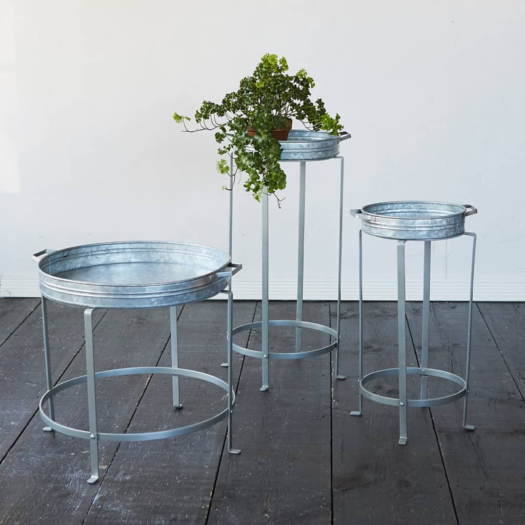 three circular silver iron plant stands