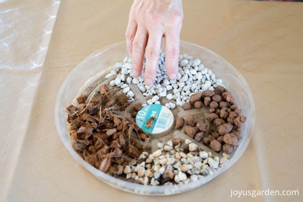 a hand hovers over a plastic saucer full of amendments to lighten succulent soil