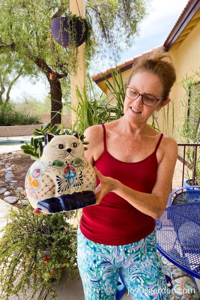 nell foster holds a cute talavera cat planter with a small jade plant planted in on her patio