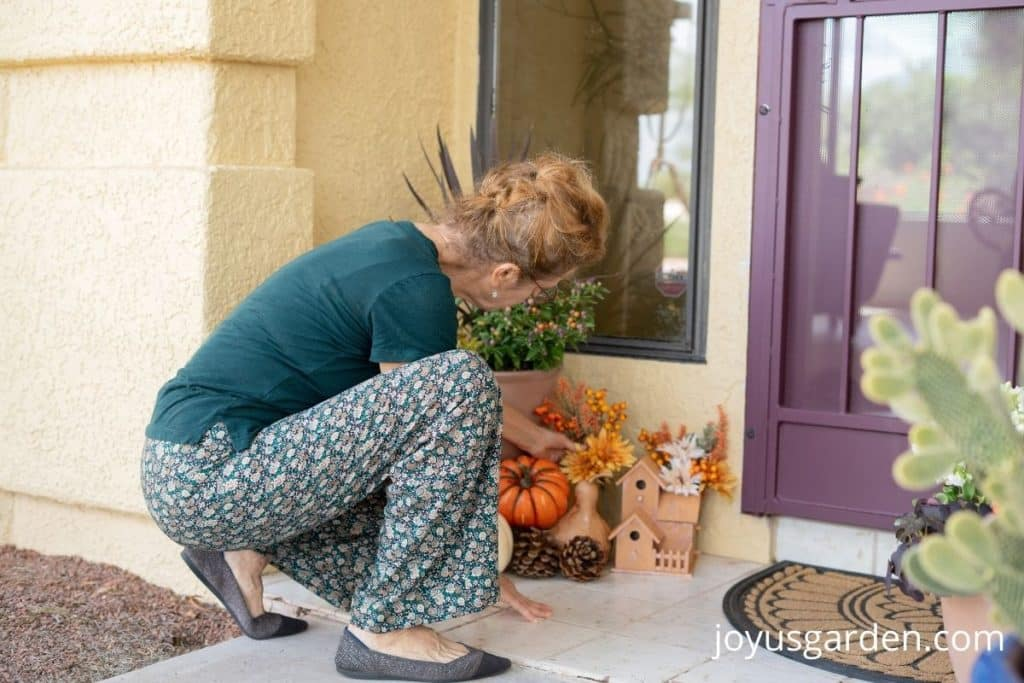 a women placing fall flowers on the front porch