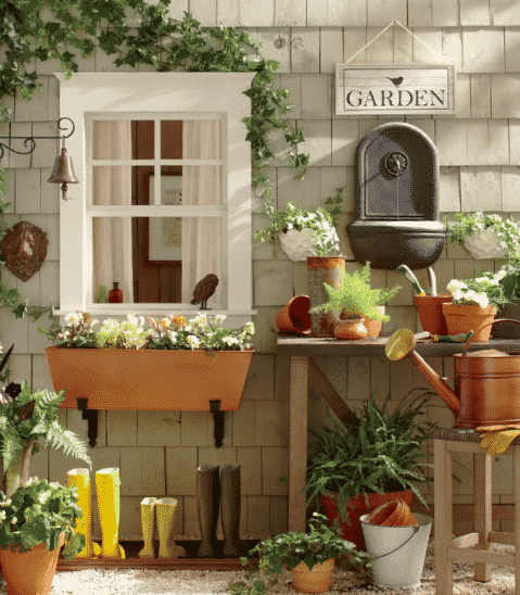 a window box planter with plants with an assortment of other pots and plants outside of a house