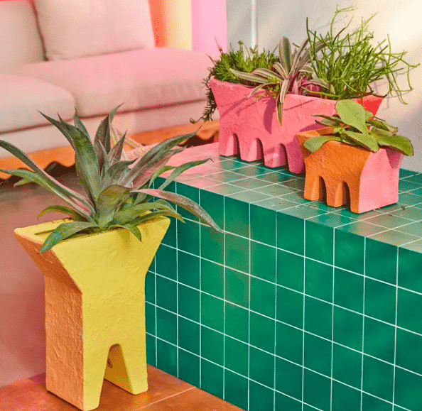 planter box in bright colors of yellow, orange, and pink with a mix of plants potted inside
